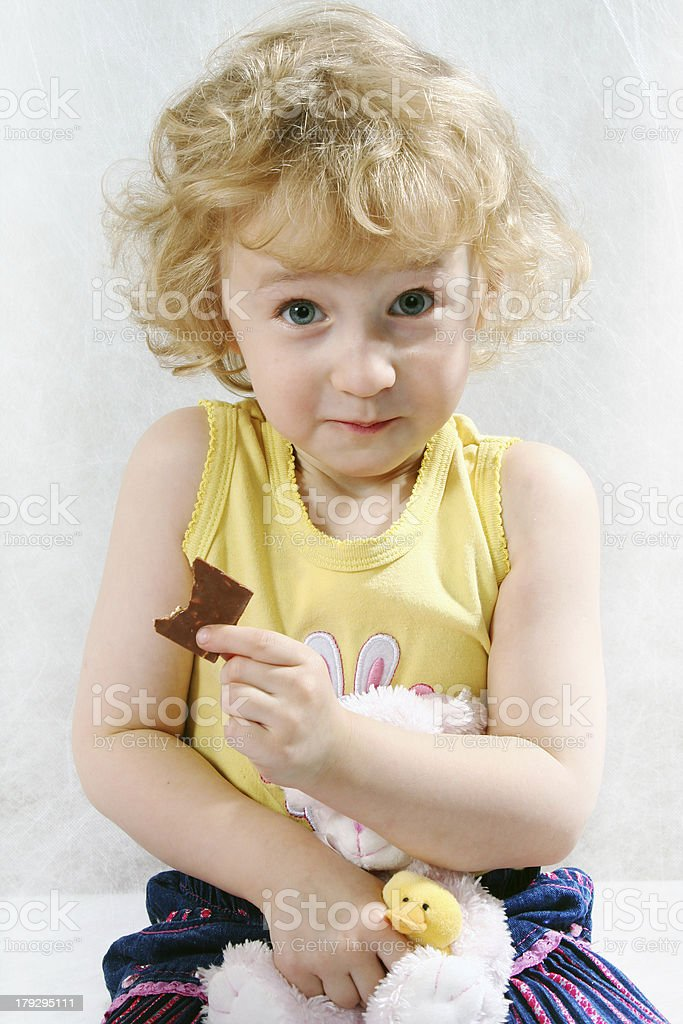 little blonde curly sitting girl on the white with toy royalty-free stock photo