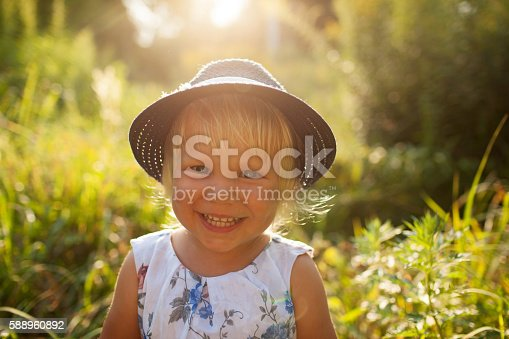 istock Little blonde girl in a blue hat 588960892