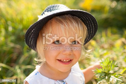 istock Little blonde girl in blue hat 588962354
