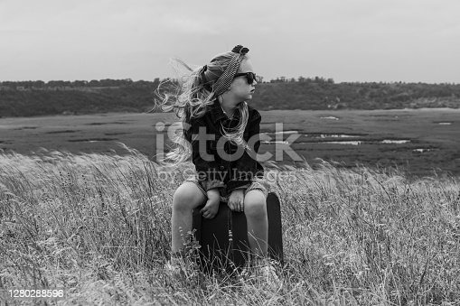 Little blonde girl in denim jacket, black sunglasses with vintage suitcase in wild grass field. Stylish hitchhiker child long hair countryside landscape trip. Kid walking outdoor.Black and white photo