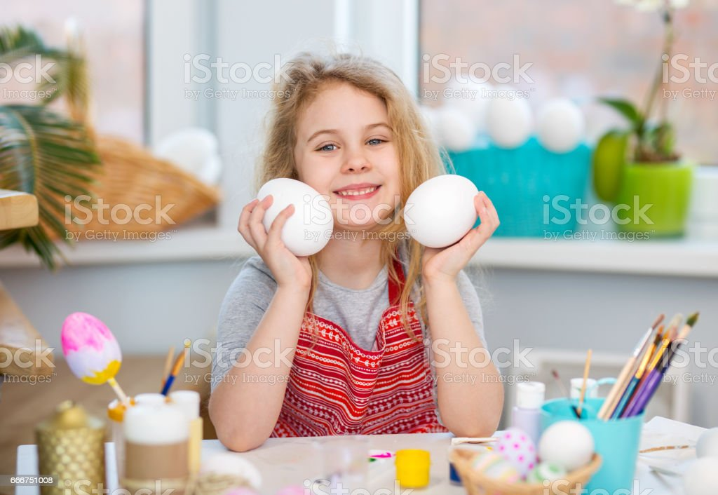 Little blonde girl showing eggs before coloring for Easter holiday at home foto stock royalty-free