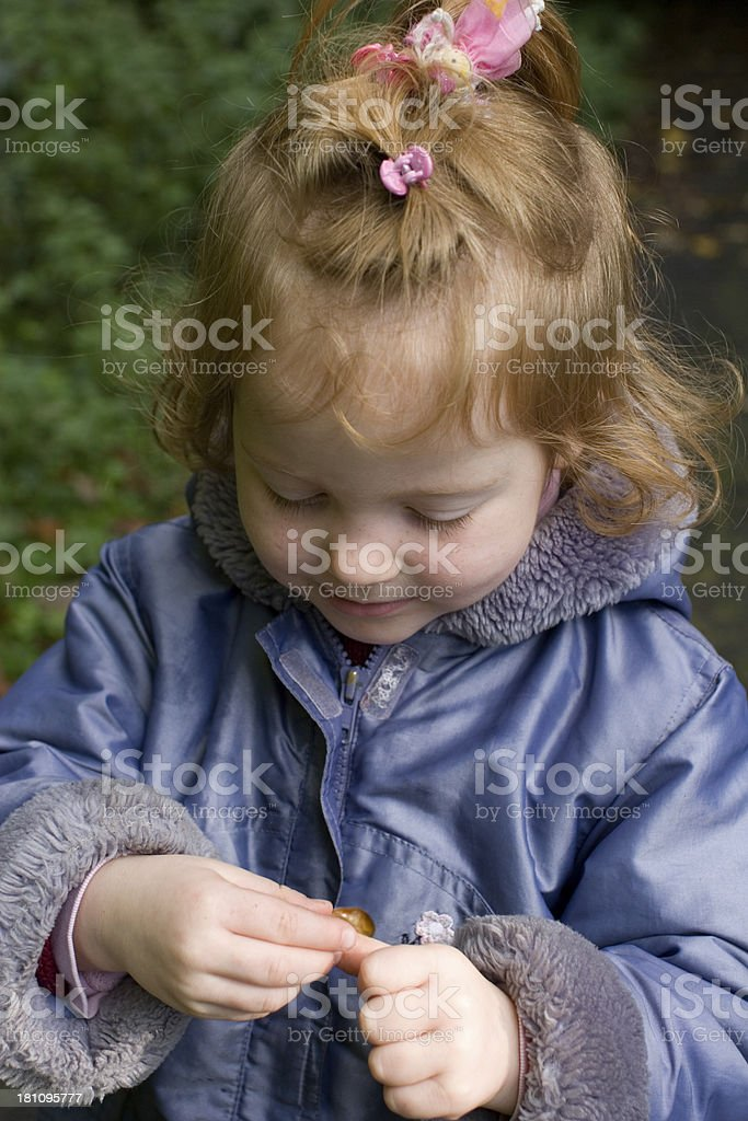 """Little blonde girl studying a snail """"Young girl in blue coat, studying the snail she holds cautiously in her hands."""" Analyzing Stock Photo"""