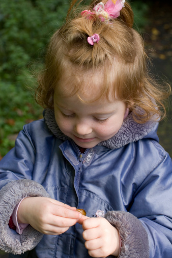 Little Blonde Girl Studying A Snail Stock Photo - Download Image Now