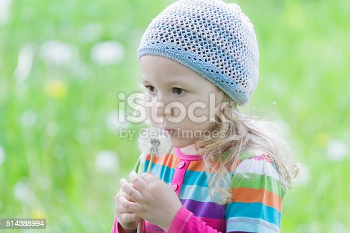 Little blonde girl wearing striped knitted hat is blowing on white puffy dandelion seed head at her hand