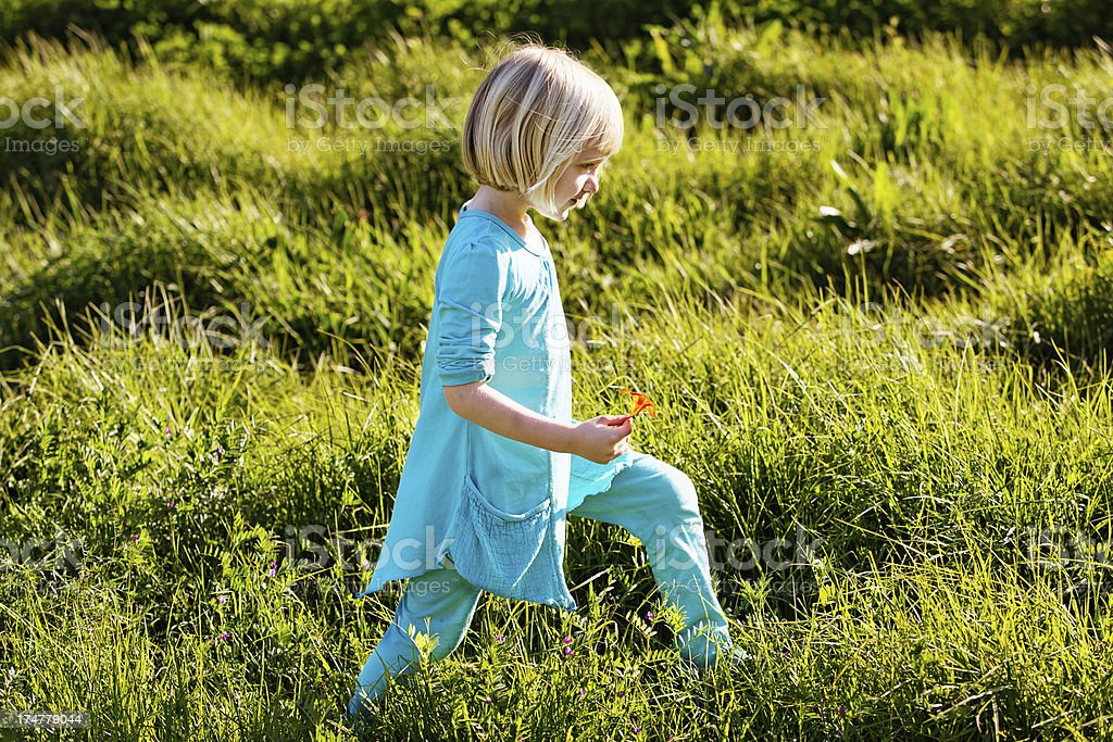 Little blonde in turquoise blue striding through long grass stock photo