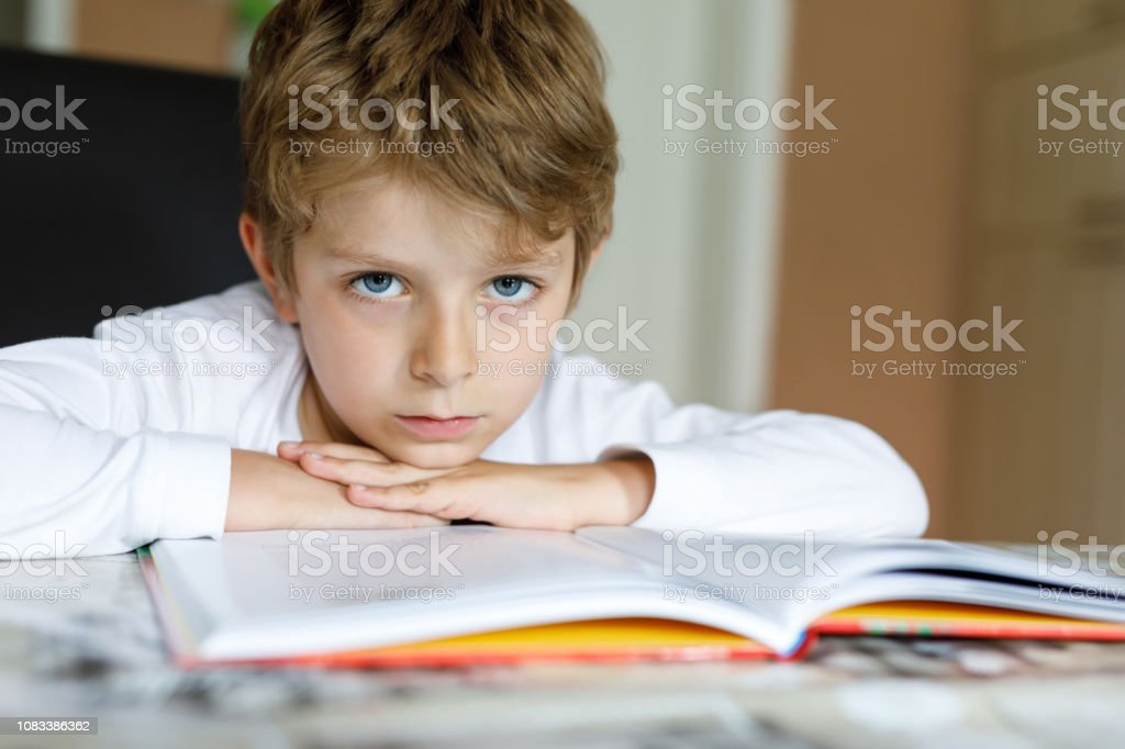 Little blonde school kid boy reading a book at home. Child interested...