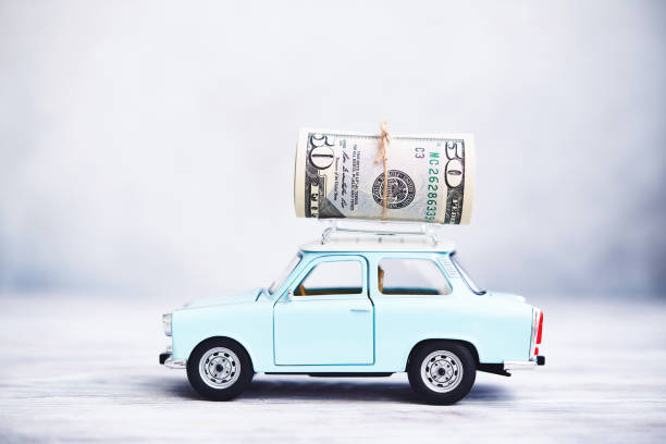 Little blue car with cash roll on roof rack stock photo