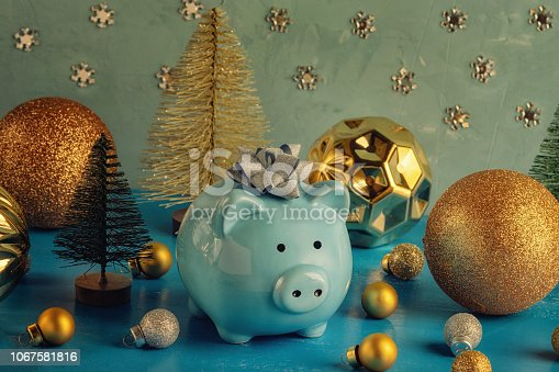 istock Little blue piggy bank with a bow on his head. Nearby are small decorative Christmas trees and a lot of golden balls of different sizes. The symbol of the new year. Holiday photography. 1067581816