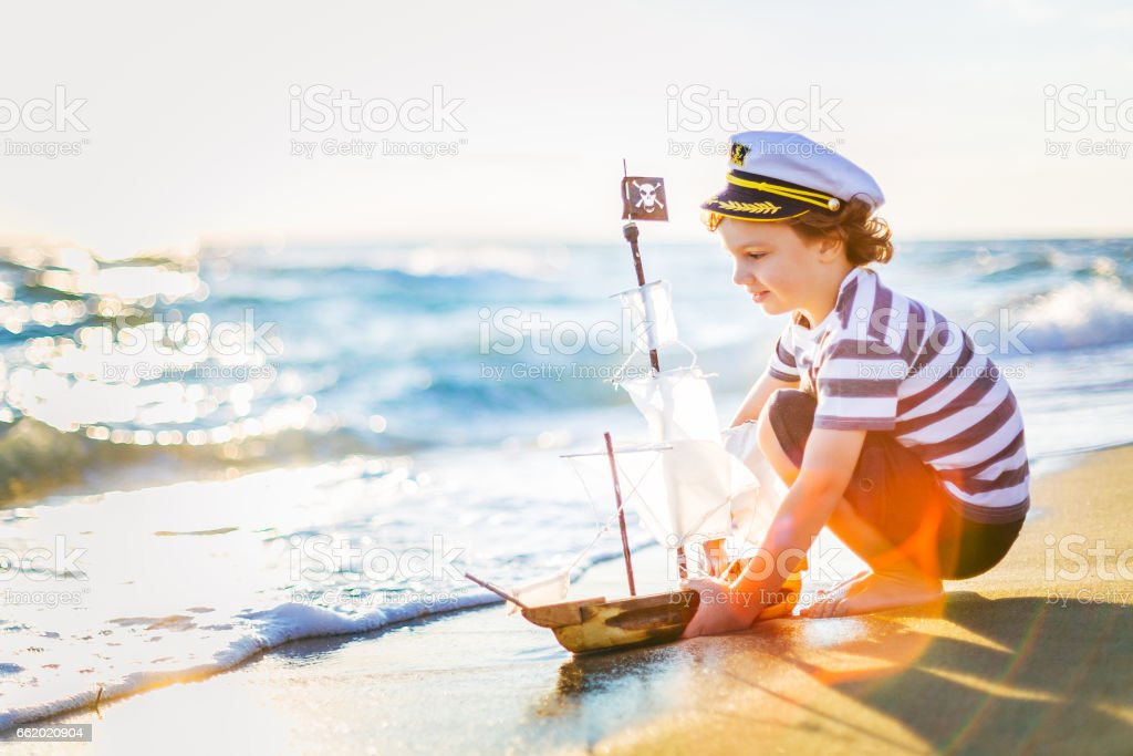 Cute little boy playing with his handmade toy boat on the beach, on...