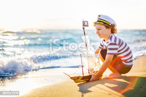 Cute little boy playing with his handmade toy boat on the beach, on an early summer morning