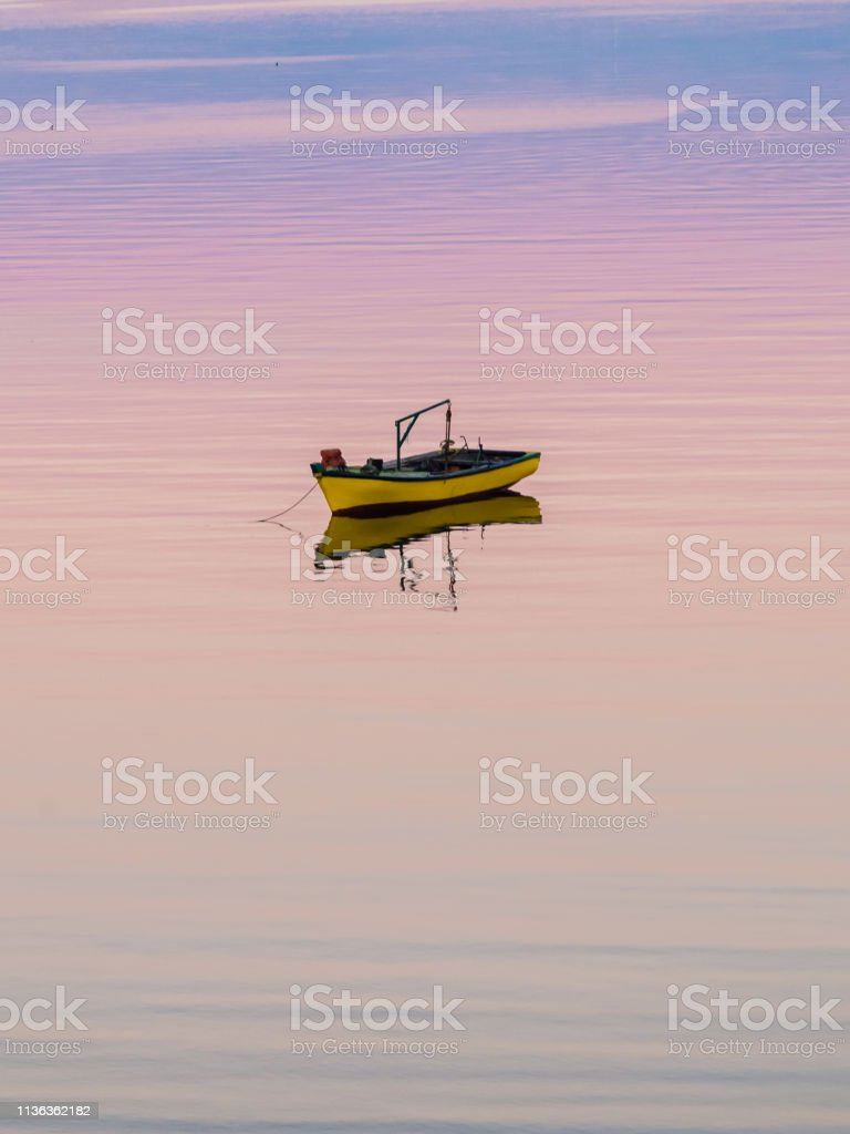 Little boat floating on the calm water under amazing sunset in...