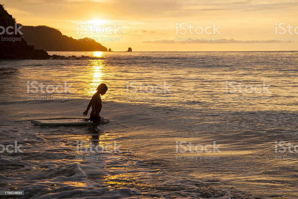 Little bodyboarder, surfer in evening light royalty-free stock photo