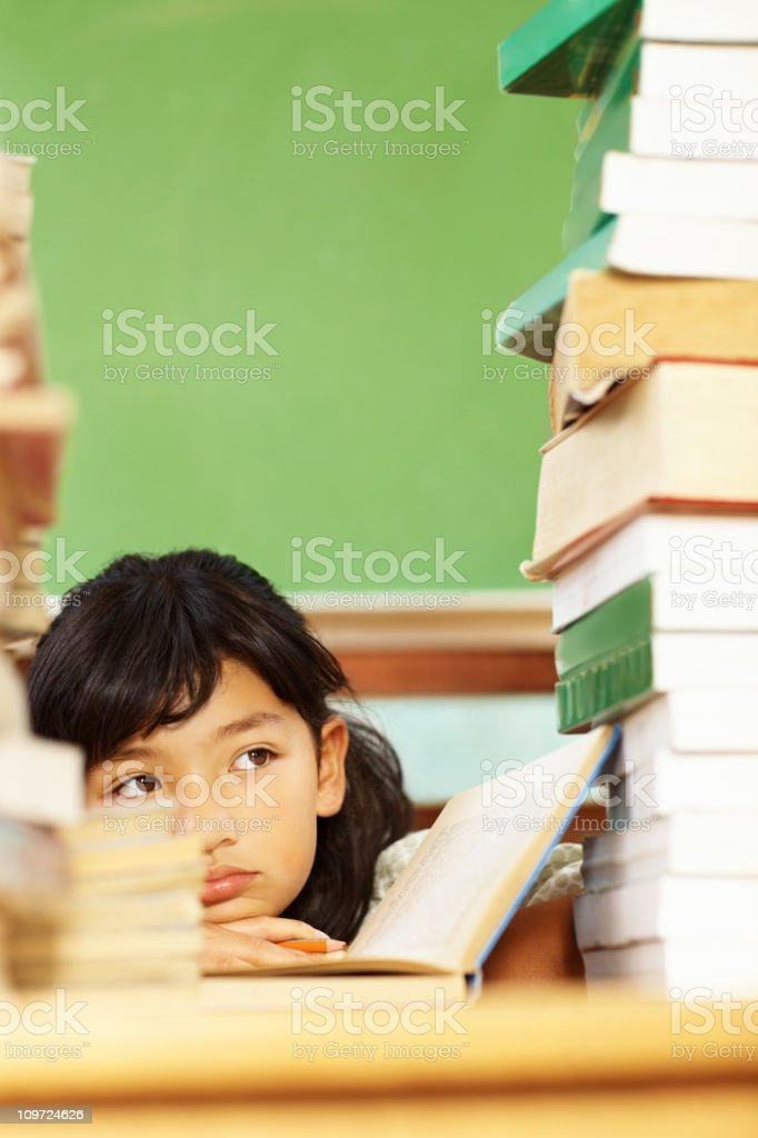 Little bored Asian girl sitting amidst a stack of books stock photo