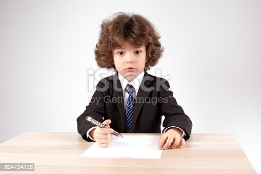 Little boss with a clean sheet of paper and a pen. Gray background. Close-up