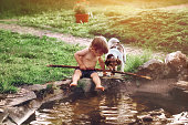 little boy 2 years old sits on shore of pond in village in his hand stick, next to friend is dog Jack Russell on sunny summer day