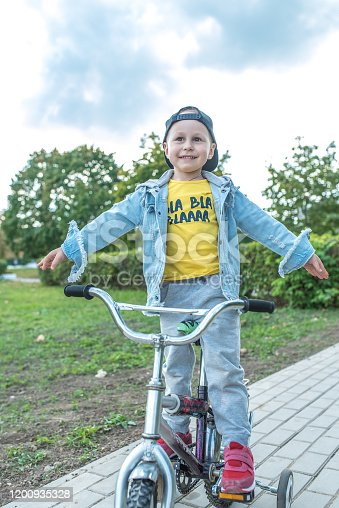 Little boy 3-5 years old, children s bike, weekend breaks, education and training, first lessons of skiing. In summer in city. Casual clothes, jeans. Happy smiling rejoices and has fun.