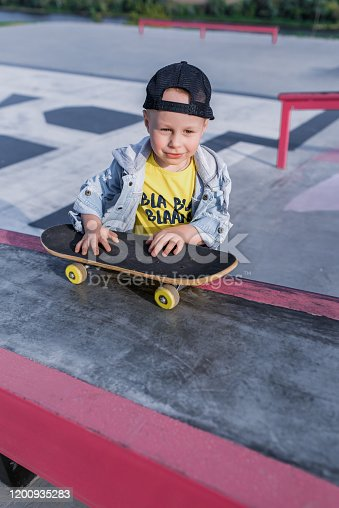 Little boy 3-5 years old, children's skate, skateboard, weekend breaks, education training, first steps on the board. In summer in city. Casual clothes, jeans. Happy smiling rejoices and has fun