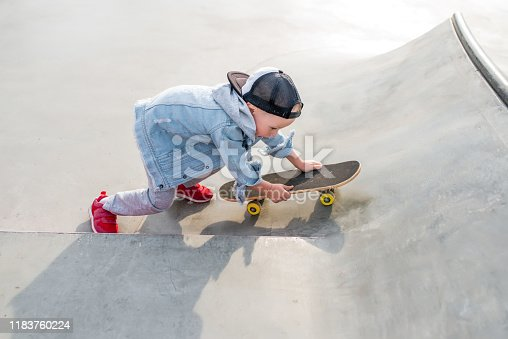 Little boy 3-5 years old, in summer on sports field in city, autumn on street, practicing skateboarding, casual wear, free space for text, baseball cap, jeans. Weekend break