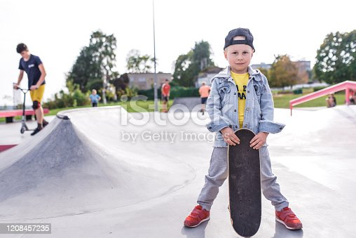 little boy 3-5 years old, stands with skateboard, summer on sports ground, learns to ride skateboard, casual wear, jeans, pants, a baseball cap. Free space for copy text. Background kids teens