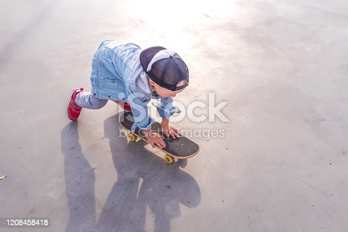 Little boy 3-5 years old, view from the top, in summer on sports ground, learning to ride skateboard, casual wear, jeans, pants, a baseball cap. Free space for copy text.