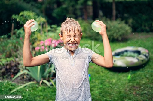 Funny little boy about to splash his head with water balloons.