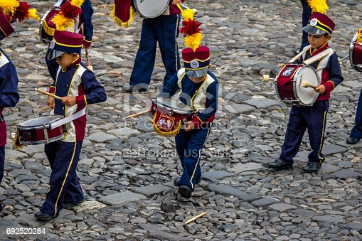 istock Little Boy accidentally drops his drum stick during Marching Band Parade - Antigua, Guatemala 692520284
