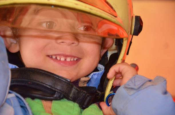 Little boy acting like a fireman. Boy putting fire helmet on head. Dreaming of future profession. Fire safety, life protection lessons. Close-up stock photo