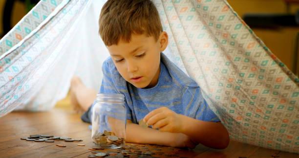 Little boy adding coins to jar. stock photo