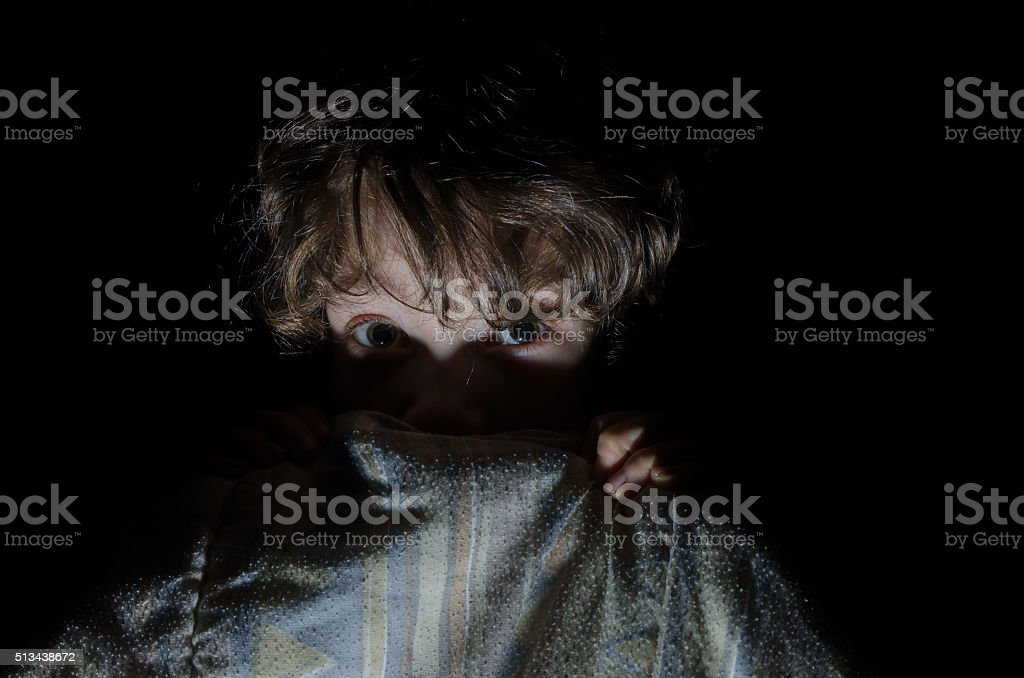 Little boy afraid hidind behind his bed sheets stock photo