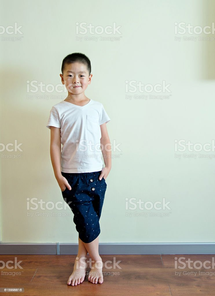 Little boy against wall stock photo