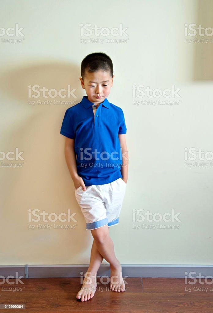 Little boy against wall stock photo