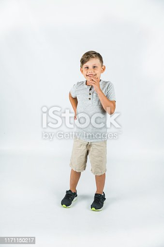 Little boy age 6 with autism on a white background with lots of copy space. Full length portrait.