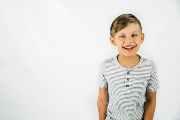 kleiner junge im alter von 6 jahren mit autismus auf weißem hintergrund mit viel kopierplatz - autismus stock-fotos und bilder