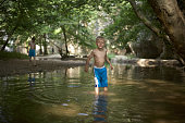 Little boy aged 5 or 6 or 7 standing in shallow water in forest in mediterranean country in summer time sunny relaxed mood teenage boy in background