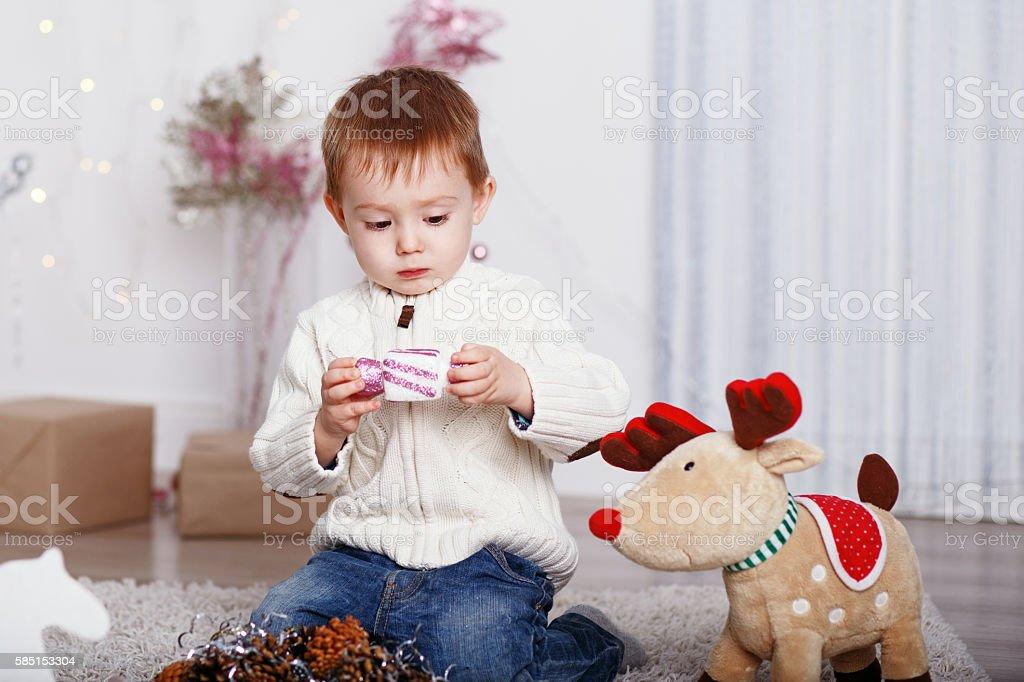 Little boy among Christmas decorations stock photo
