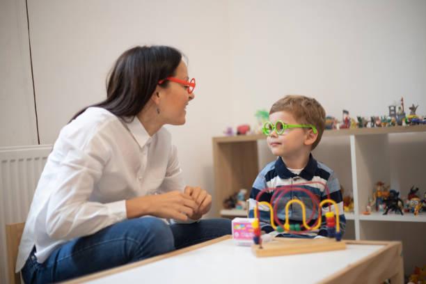 kleiner junge und ein therapeut mit einer spieltherapie-klasse - autismus stock-fotos und bilder