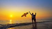 A little boy and father play launching a kite at sunset, summer vacation concept