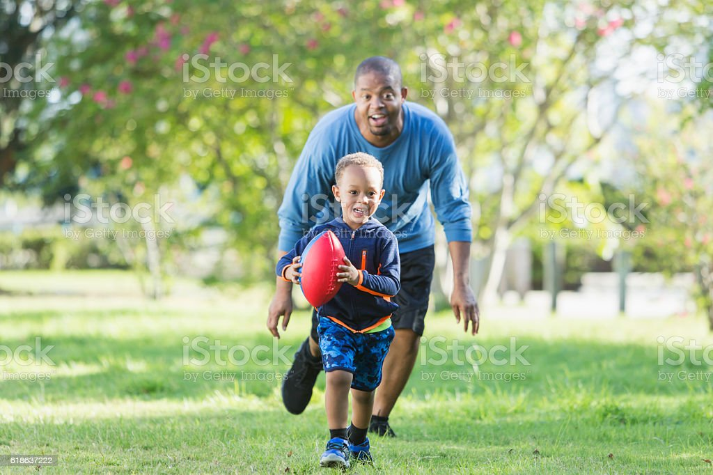 Little boy and father playing in the park with ball stock photo