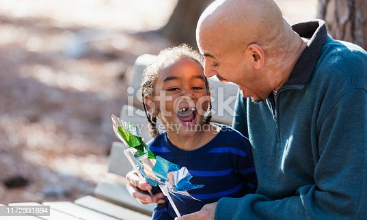 An Hispanic father playing with his little boy at the park with pinwheel toys. Dad is a mature man in his 50s with a shaved head. His 4 year old son is mixed race Hispanic and African-American with cornrow braids. They are looking at each other, laughing.