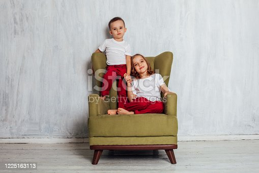 1062609644 istock photo little boy and girl are brother and sister sit on a green Chair 1225163113