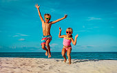 little boy and girl dance at beach, happy kids enjoy vacation at sea