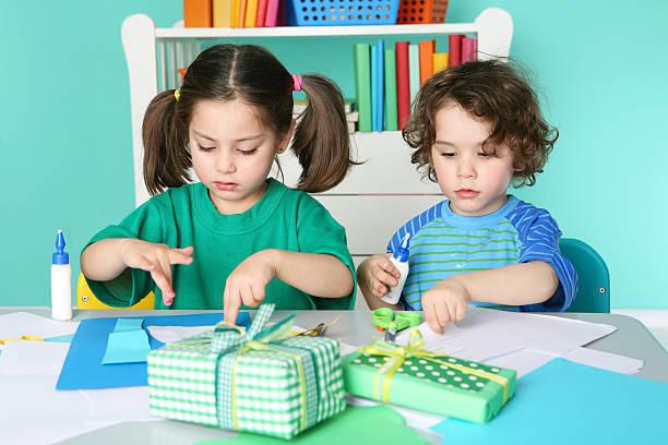 kleine jungen und mädchen tun kunsthandwerk - bastelkarton stock-fotos und bilder