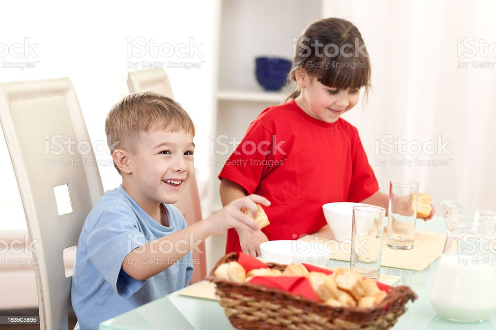 Little boy and girl eating breakfast royalty-free stock photo