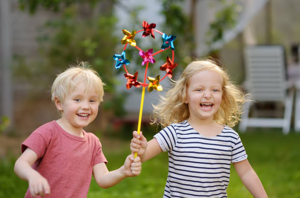 kleine jungen und mädchen, die spaß beim spaziergang. glückliches kind mit windrad. - sommerfest kindergarten stock-fotos und bilder