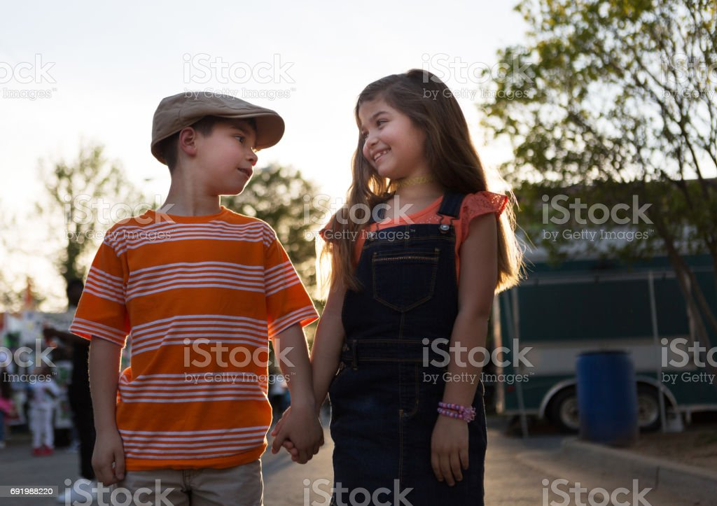 Little boy and girl holding hands stock photo