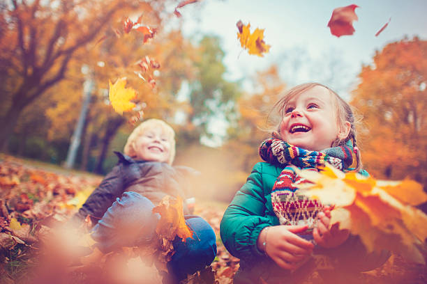Little boy and girl in autumn park stock photo