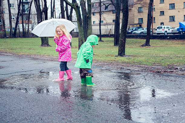 Little boy and girl in puddle stock photo