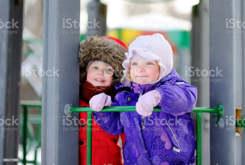 Little boy and girl in winter clothes having fun in outdoors playground stock photo