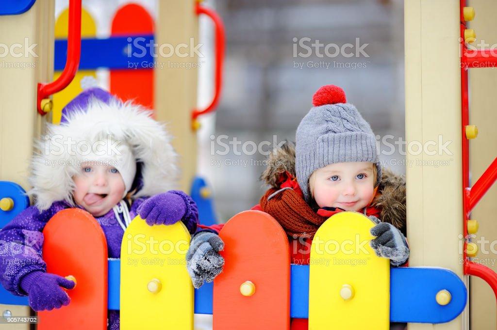 Pequeño niño y niña en ropa de invierno que se divierten en el patio al aire libre - foto de stock