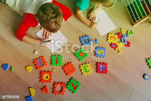 157230867istockphoto little boy and girl learn to write and calculate numbers 877341516